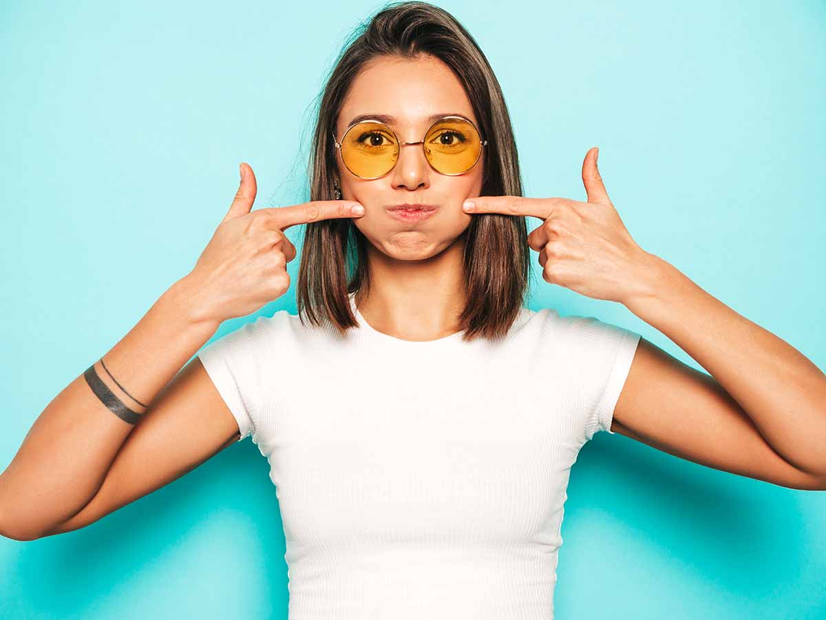 Young beautiful woman looking at camera.Trendy girl in casual summer white T-shirt and yellow skirt in round sunglasses. Positive female shows facial emotions.Funny model blowing her cheeks.Puff out